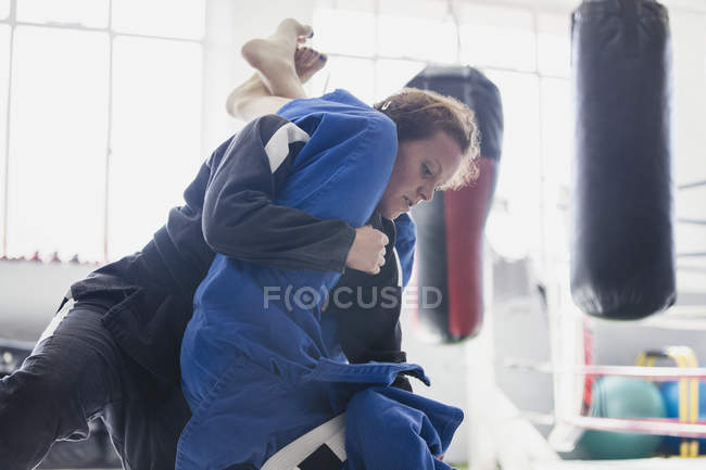 Determined woman practicing judo, tackling in gym — Stock Photo