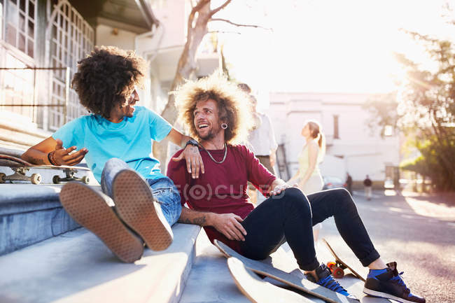 Male friends with skateboards talking on sunny urban stairs — Stock Photo