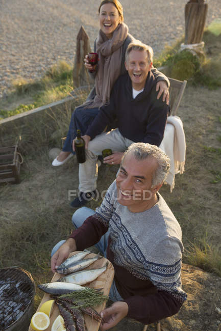 Portrait smiling mature friends barbecuing and drinking wine on beach — Stock Photo