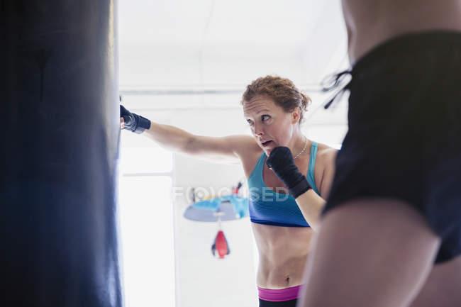 Решительная, жесткая женщина боксер бокс на боксерскую грушу в тренажерном зале — стоковое фото