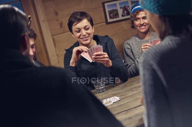 Freunde spielen Karten am Kabinentisch — Stockfoto