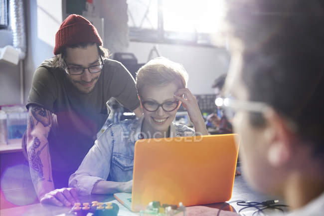 Designers working at laptop in workshop together — Stock Photo
