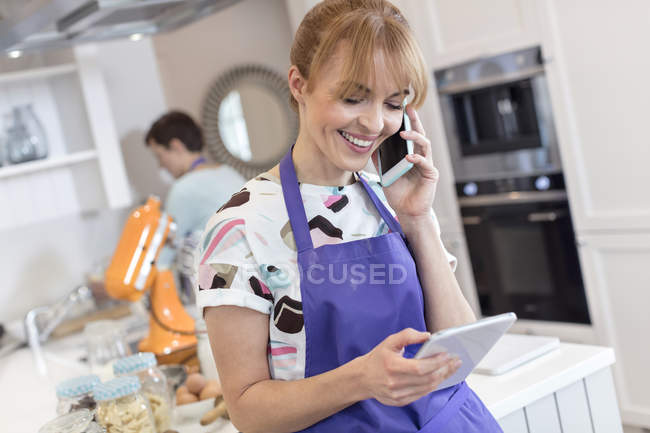 Smiling caterer working, talking on cell phone and using digital tablet in kitchen — Stock Photo
