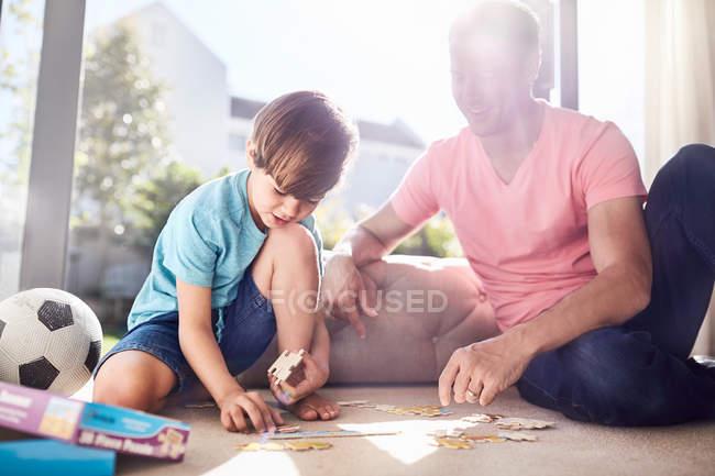 Отец и сын, монтаж головоломки штук на этаже — стоковое фото