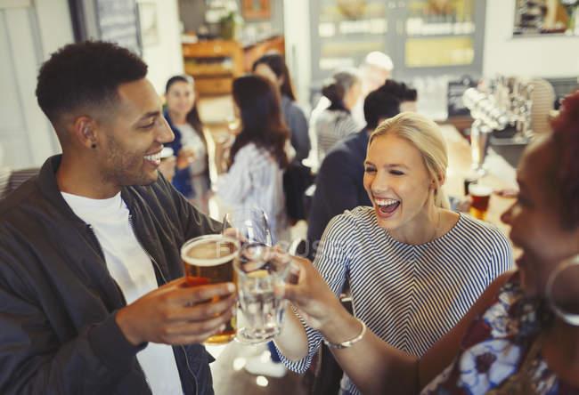Amigos risonhos brindam cerveja e copos de vinho no bar — Fotografia de Stock