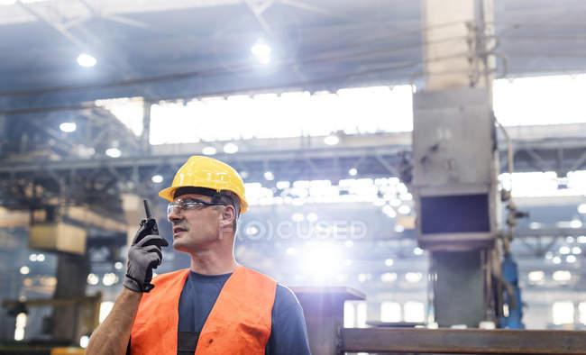 Steel worker using walkie-talkie in factory — Stock Photo
