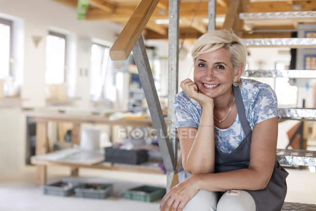 Portrait artiste souriant sur les marches en studio — Photo de stock