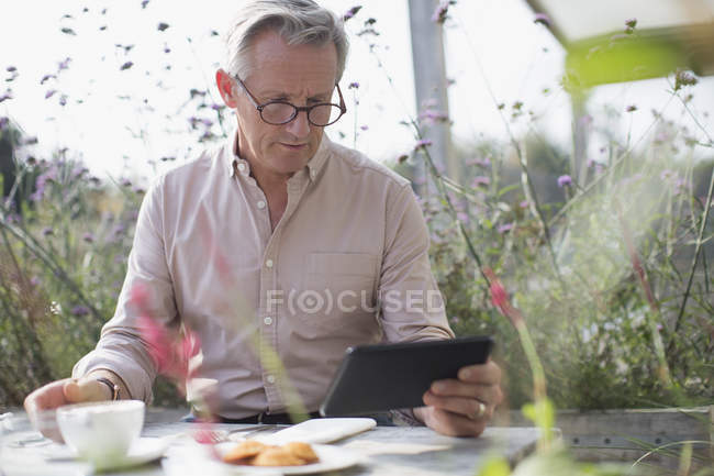 Senior man using digital tablet and drinking coffee at patio table — Stock Photo