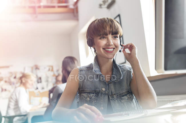 Smiling design professional using headset with microphone in office — Stock Photo