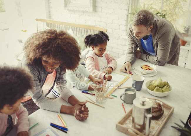 Multi-ethnic young family coloring with markers at table — Stock Photo