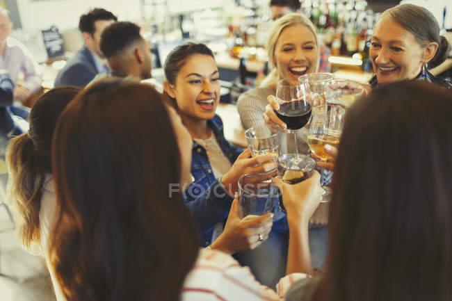 Энтузиастки празднуют с друзьями, пьют пиво и пьют бокалы в баре — стоковое фото