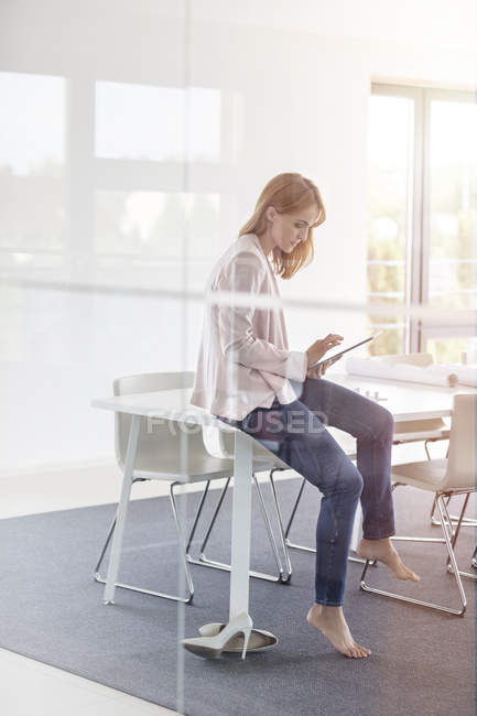 Barefoot businesswoman using digital tablet in conference room — Stock Photo