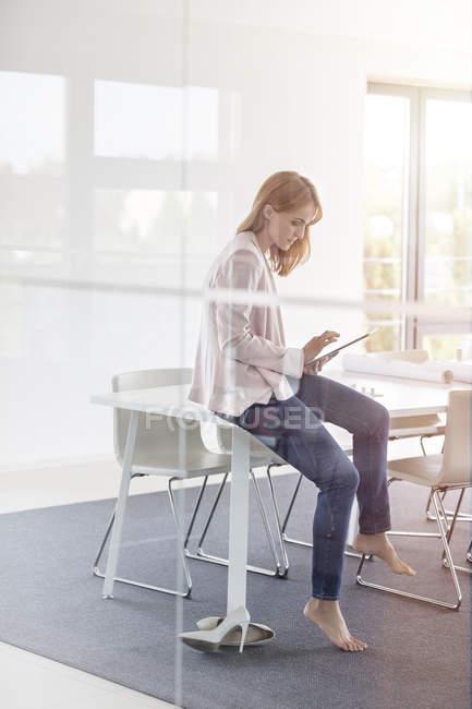 Barfüßige Geschäftsfrau nutzt digitales Tablet im Konferenzraum — Stockfoto