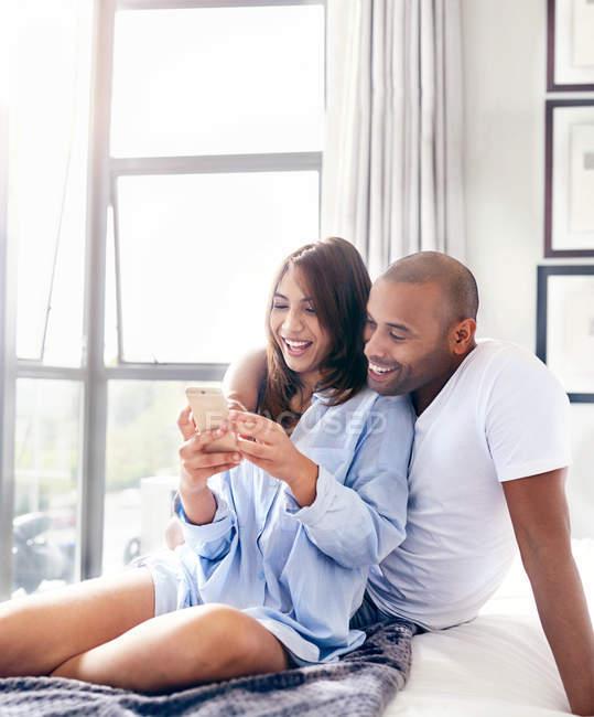 Улыбающаяся пара смс с сотовым телефоном на кровати — стоковое фото
