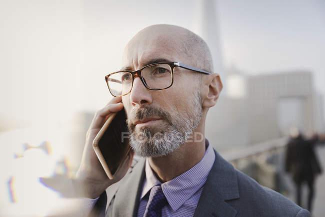 Chiudi un serio uomo d'affari che parla al cellulare — Foto stock