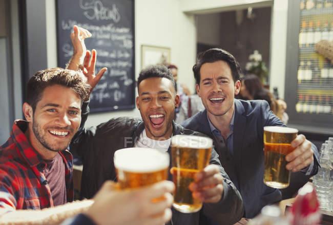 Retrato homens entusiastas amigos brindar copos de cerveja no bar — Fotografia de Stock