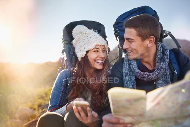 Молоді пара з рюкзаками походи перевірка карти — стокове фото
