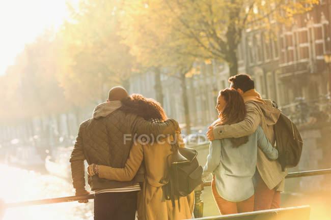 Jeunes couples embrassant sur le pont sur le canal ensoleillé d'automne, Amsterdam — Photo de stock