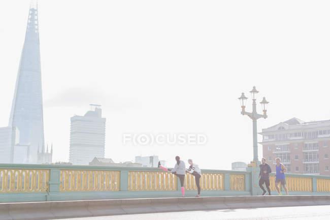 Corredores corriendo y estirándose en el soleado y nebuloso puente urbano, Londres, Reino Unido - foto de stock
