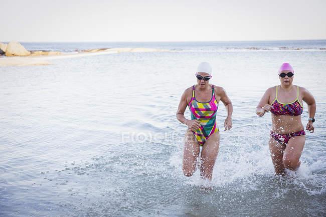 Femininos ativos nadadores executando no oceano ao ar livre — Fotografia de Stock