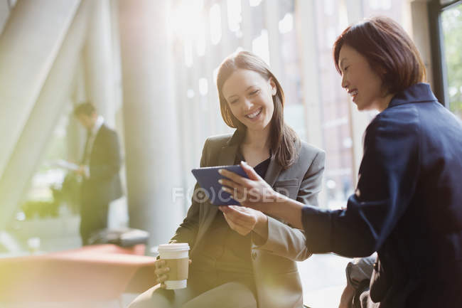 Businesswomen drinking coffee and using digital tablet in office lobby — Stock Photo