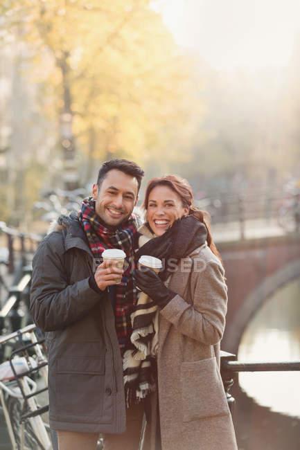 Portrait jeune couple souriant buvant du café le long du canal urbain d'automne — Photo de stock