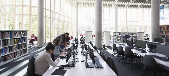 Étudiants cherchant dans les ordinateurs de la bibliothèque — Photo de stock
