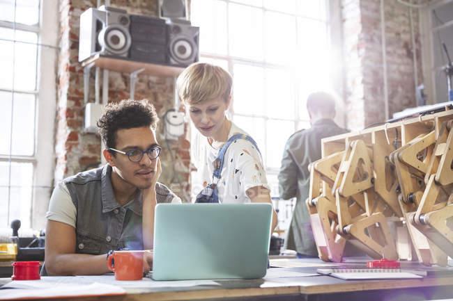 Серьезные, целенаправленные дизайнеры, работающие за ноутбуком в мастерской — стоковое фото