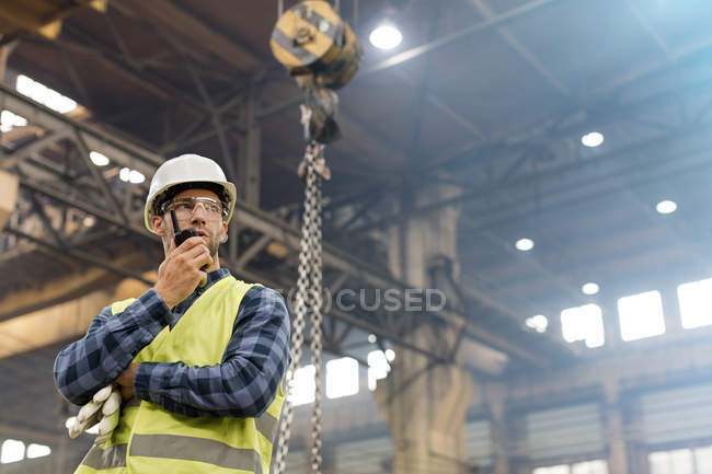 Steel worker with walkie-talkie in factory — Stock Photo