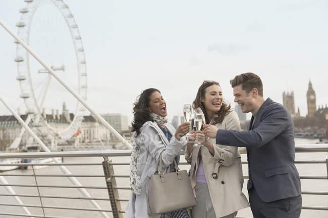 Ami enthousiaste et souriant célébrant, champagne grillé sur un pont urbain près de Millennium Wheel, Londres, Royaume-Uni — Photo de stock