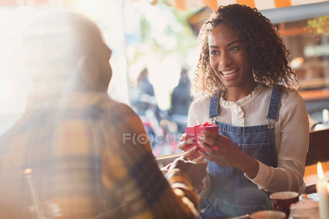 Другом, даючи подарунковій коробці здивований подругу в кафе — стокове фото