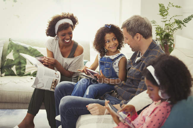 Multi-ethnic young family using digital tablets and reading magazine on sofa — Stock Photo