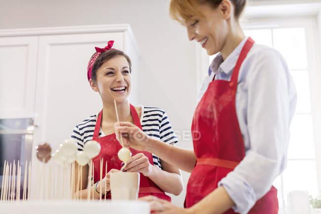 Souriant femmes traiteurs cuisson, faire éclater cupcake dans la cuisine — Photo de stock
