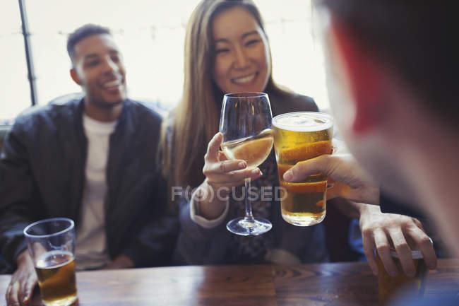 Amigos comemorando, torrar cerveja e vinho na mesa no bar — Fotografia de Stock