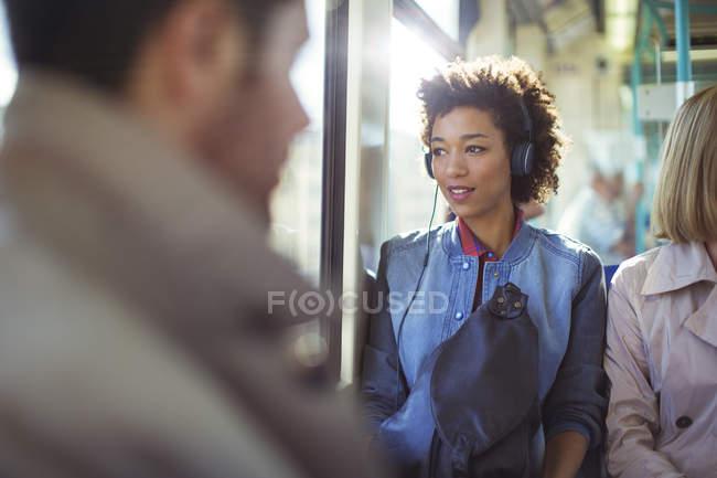 Woman listening to headphones on train — Stock Photo
