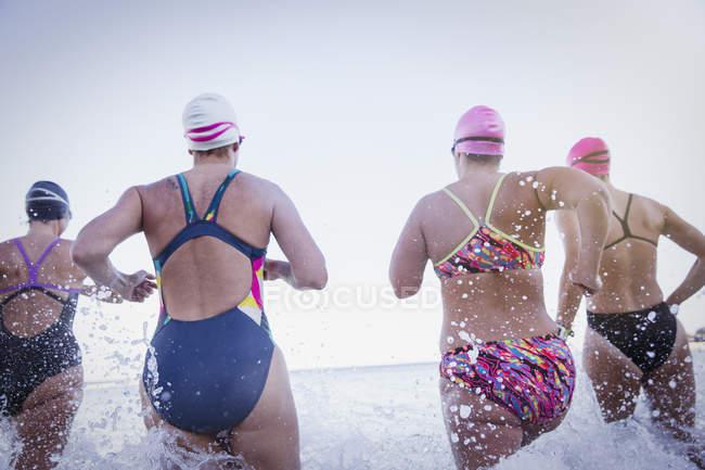 Arrière Découvre des nageurs actives féminines fonctionnant à l'océan, à l'extérieur — Photo de stock