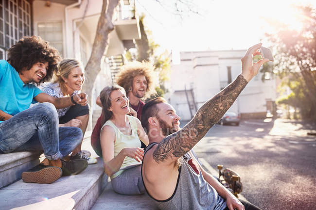 Friends hanging out taking selfie with camera phone on steps — Stock Photo