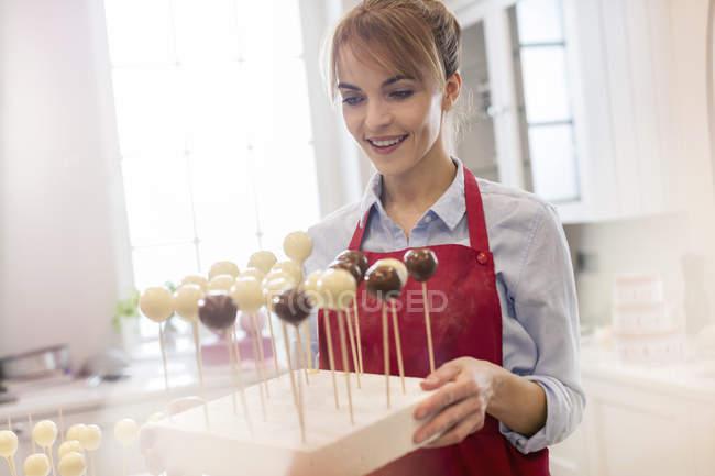 Souriant gâteau au four femme traiteur pops dans la cuisine — Photo de stock
