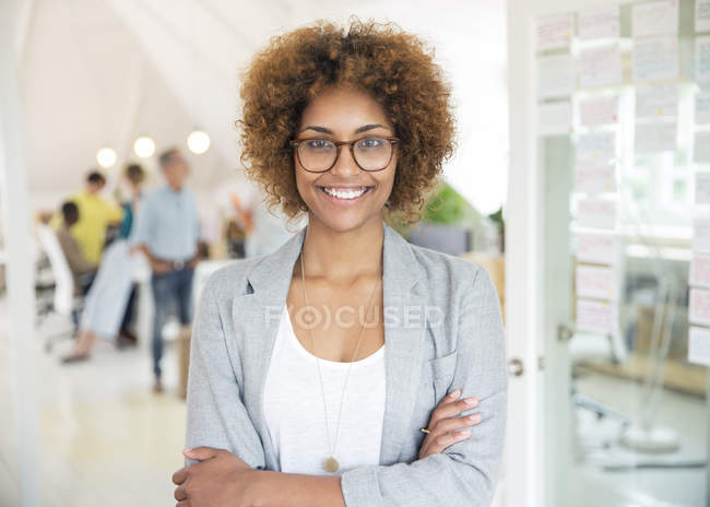 Portrait of smiling office worker with crossed arms — Stock Photo