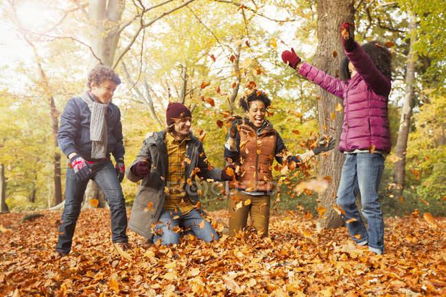 Verspielte junge Familie wirft Blätter in herbstliche Wälder — Stockfoto
