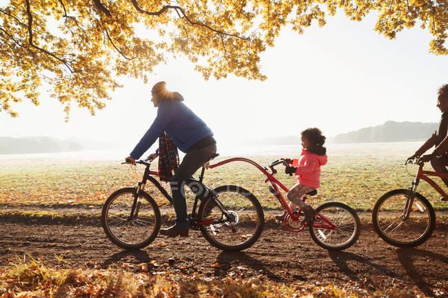 Bici padre e figlia in bici con rimorchio nel soleggiato parco autunnale — Foto stock