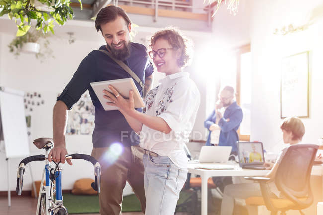 Smiling design professionals with bicycle and digital tablet talking in office — Stock Photo