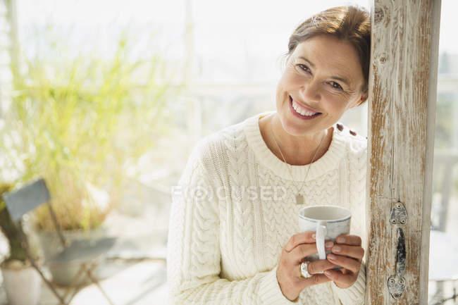 Retrato sonriente mujer madura bebiendo café - foto de stock