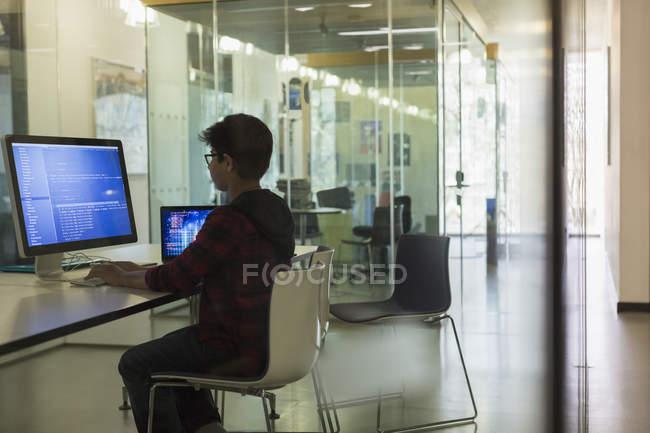 Основное внимание мальчик студент программирования на компьютере в темных классе — стоковое фото