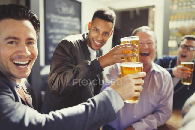 Begeisterte Männerfreunde stoßen an der Bar auf Biergläser an — Stockfoto