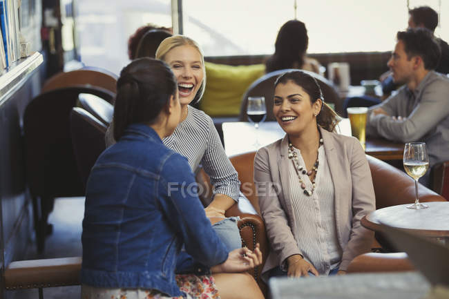 Laughing women friends talking and drinking wine in bar — Stock Photo
