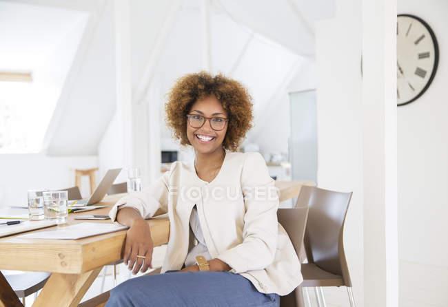 Портрет жінка, сидячи на столі в офісі і посміхається — стокове фото