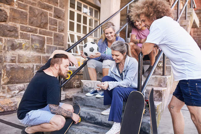 Friends hanging out using digital tablet on urban steps — Stock Photo