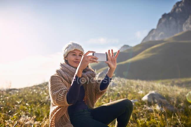 Jeune femme à l'aide de téléphone appareil photo dans la vallée ensoleillée, distante — Photo de stock