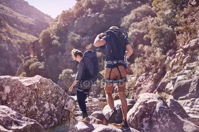 Young couple with backpacks hiking over sunny rocks — Stock Photo